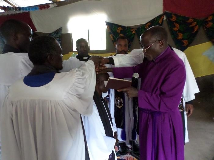 Askofu Salala akimwekea mikono Mchungaji Mteule Daniel Malale wa Mwamapuli